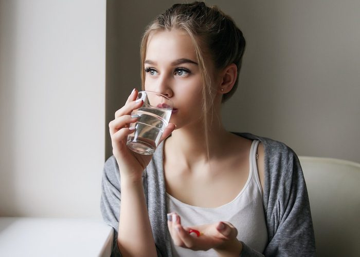 Young beautiful girl or woman take a pill or tablet with a glass of water near the window in white shirt and grey robe