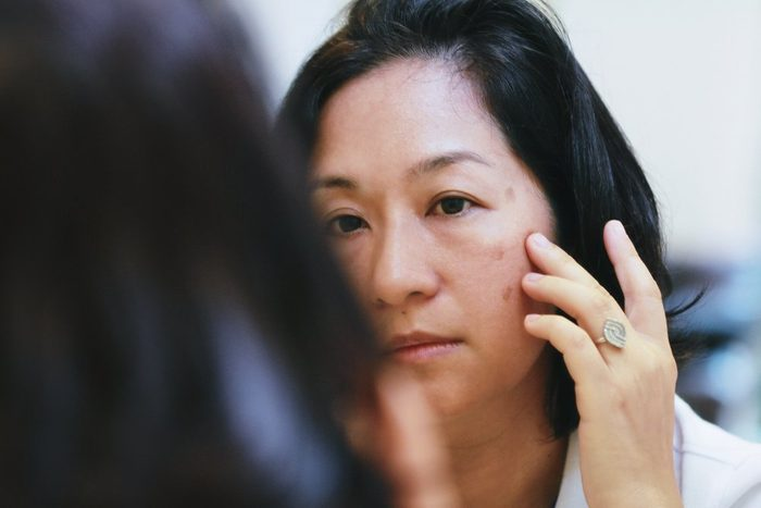 40s Asian woman looking on her face skin in the mirror and look worried or concern about the Aging skin problem.Brownish colored patches or melasma appear on the cheeks.