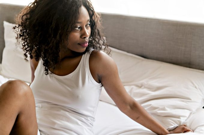 Beautiful black woman on a white bed