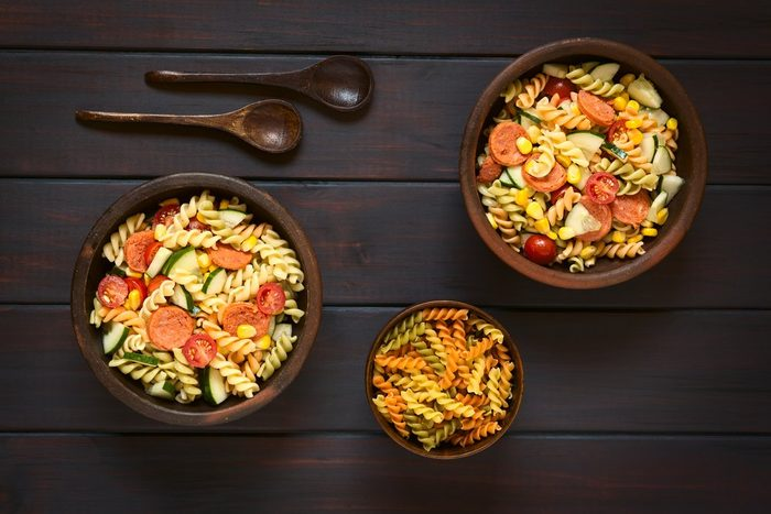 Overhead shot of two rustic bowls of pasta salad made of tricolor fusilli, sweet corn, cucumber, cherry tomato and sausage, photographed on dark wood with natural light