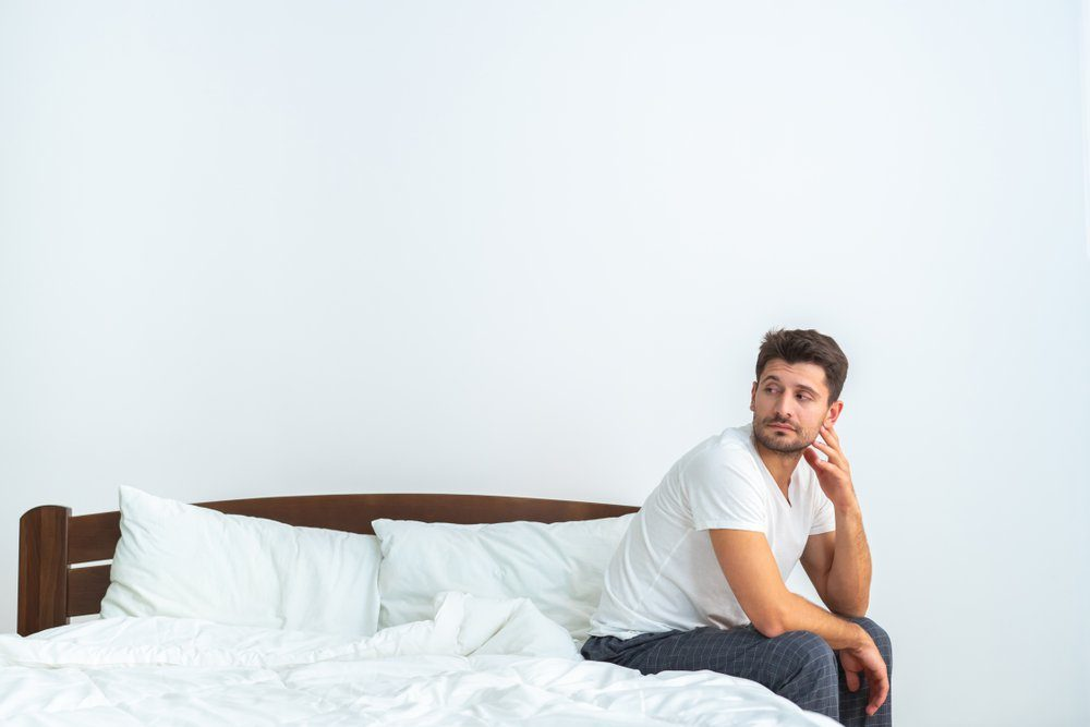 The sad man sitting on the bed on the white background