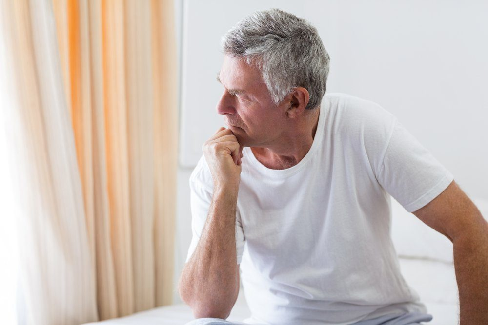 Worried senior man sitting on bed at home