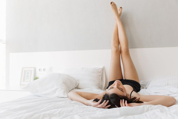 Portrait of a beautiful young woman lying on bed with legs up on bed at the bedroom