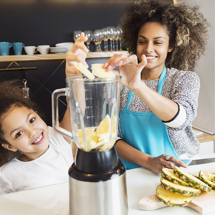 Beautiful African American woman and her daughter making a smoothie in the kitchen ;