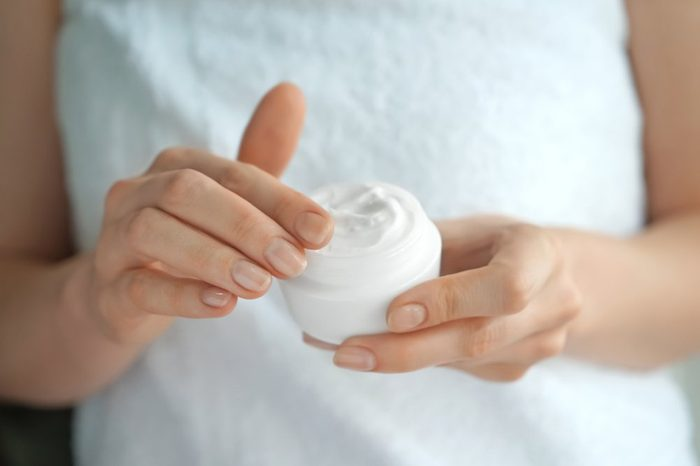 Woman applying body cream, closeup