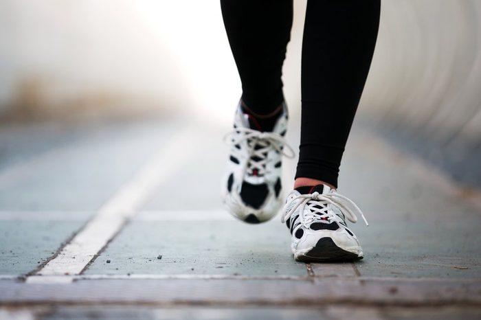 Runner feet walking on road closeup on shoe. woman fitness jog workout wellness concept.