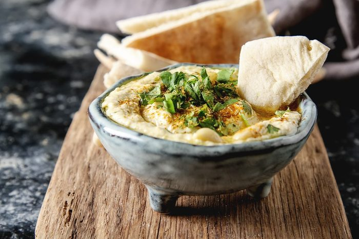 Classic hummus with herbs, olive oil in a vintage ceramic bowl and pita bread. Traditional Middle Eastern cuisine. Dark background