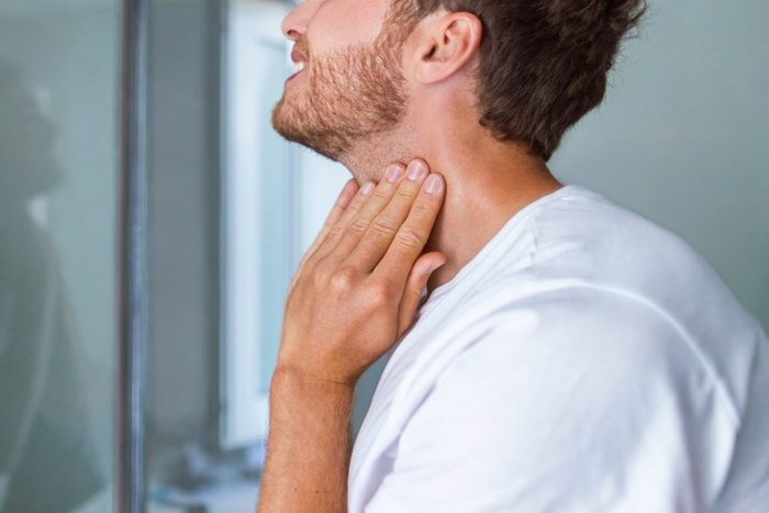 Thyroid self-exam checkup. Young man touching his neck at home bathroom doing self-check of his thyroid gland looking at mirror for early signs of health problem.