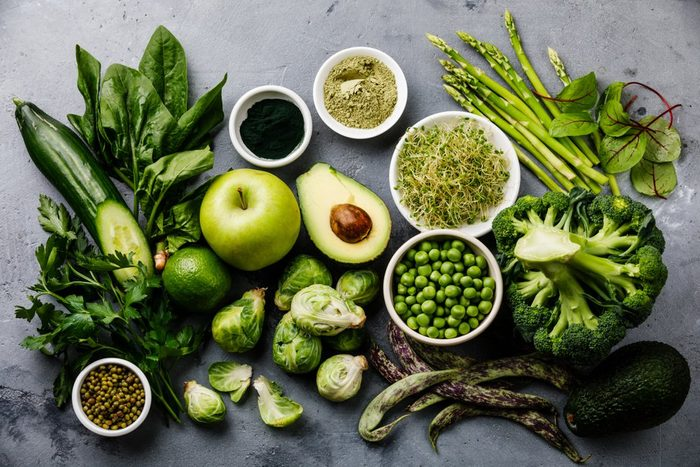 Healthy Green food Clean eating selection Protein source for vegetarians: avocado, asparagus, apple, broccoli, spinach, spirulina, green peas on gray concrete background