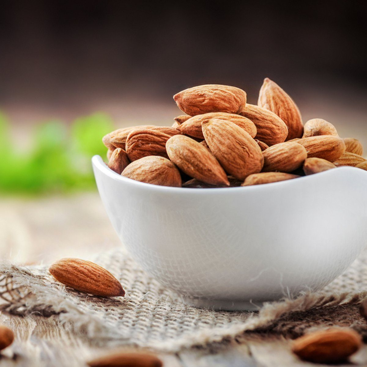 Almonds in white porcelain bowl on wooden table.