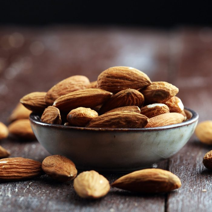 Almonds on a rustic wooden table and almond in bowl