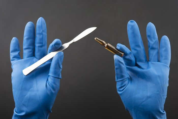 Medical scalpel and vial for injection in hands wearing blue gloves