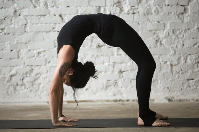 Young yogi attractive woman practicing yoga concept, stretching in Urdhva Dhanurasana exercise, Bridge pose, working out, wearing sportswear, black tank top and pants, full length, white background