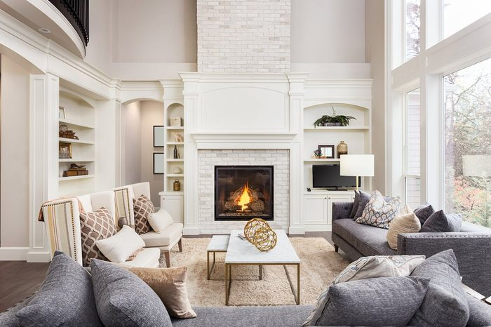 Beautiful living room interior with hardwood floors and fireplace in new luxury home. Large bank of windows hints at exterior view