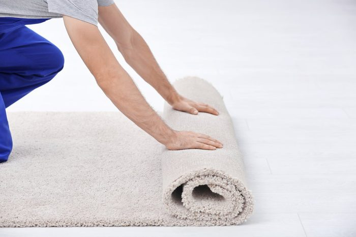 Male worker unrolling carpet indoors