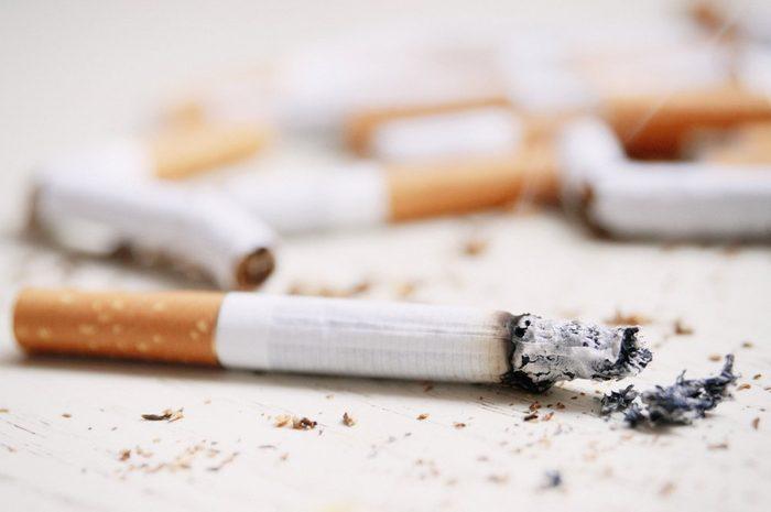 Burning cigarette on the background of broken cigarettes