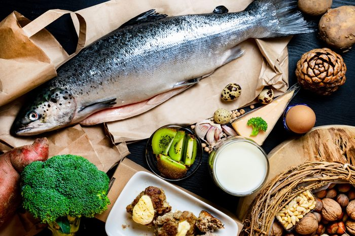 Products containing phosphorus salmon fish, pine nuts, peanuts, anchovy, cheese, milk, eggs, broccoli, kiwi, potatoes, meat, beans garlic on a round cutting board and black wooden background