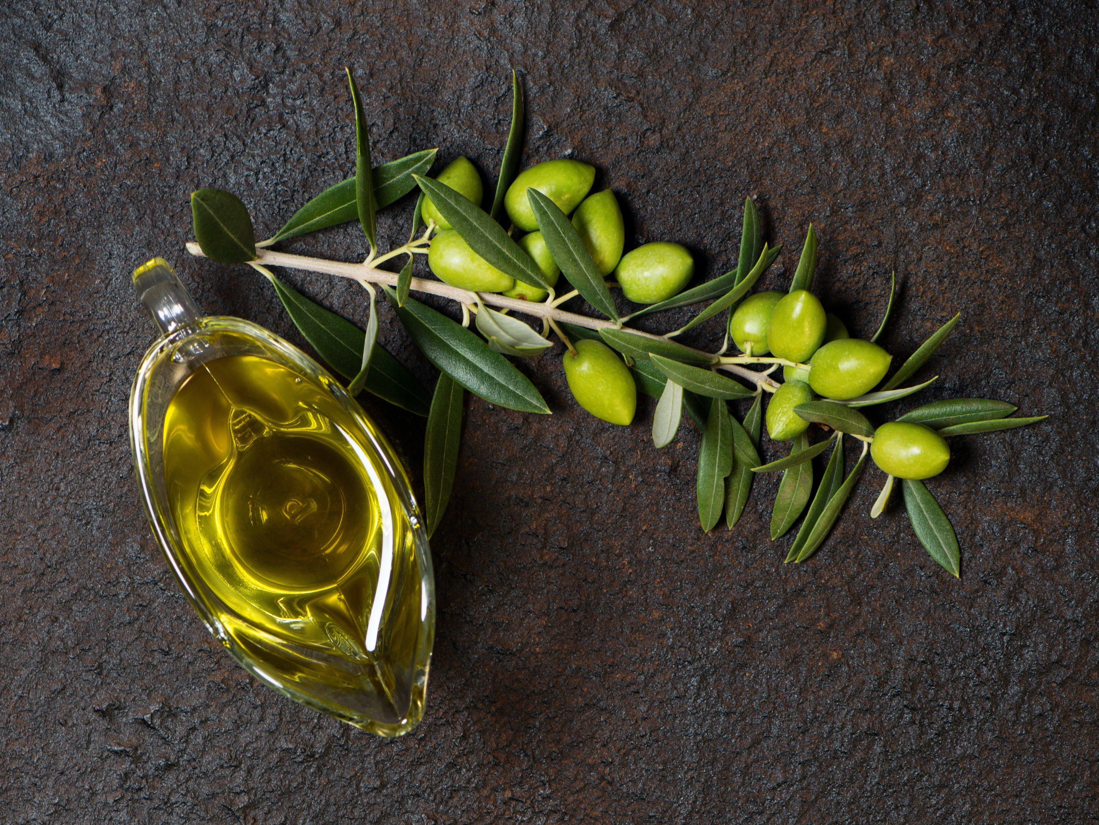 Top view of branch with green olives and glass sauceboat of olive oil on a black grunge metal background.