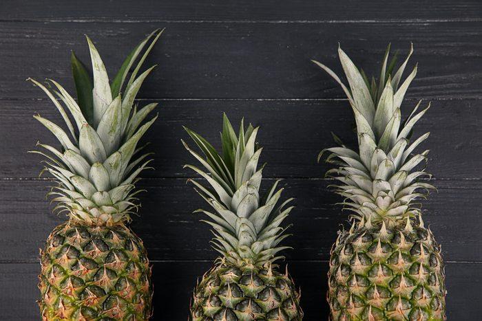 Fresh pineapples on dark wooden background