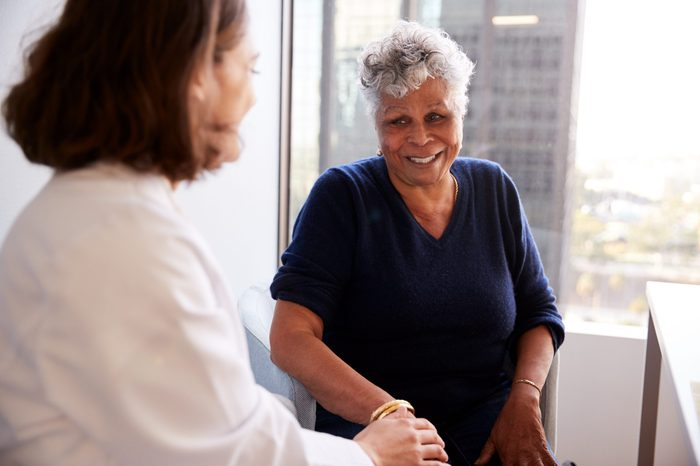 Female Doctor In Office Reassuring Senior Woman Patient And Holding Her Hands