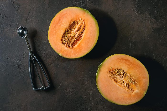 Half of ripe organic Cantaloupe melon with seeds and spoon over dark brown texture background. Flat lay, space