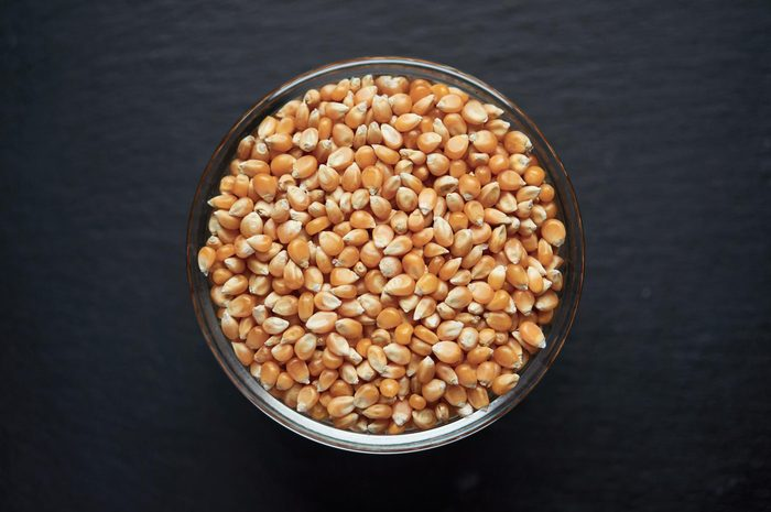 Corn seeds in a bowl on dark background. Vegetarian organic food.