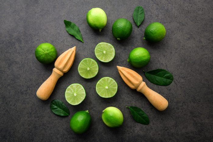 Fresh limes and wooden juicer on dark background. Top view with copy space