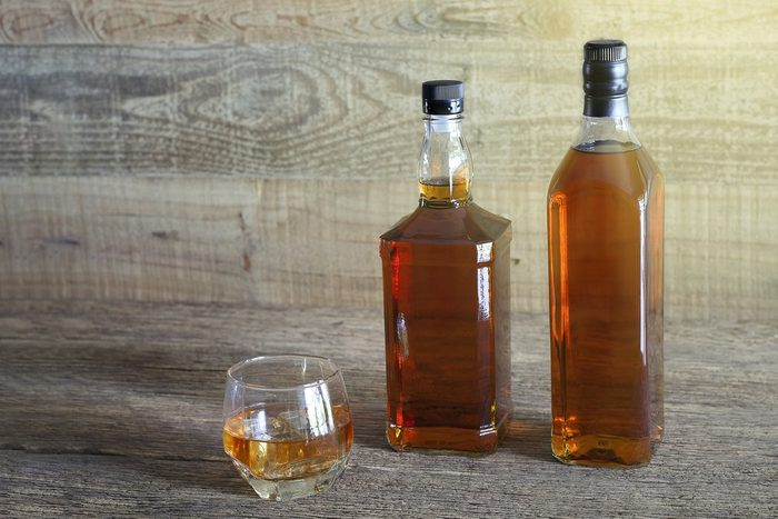 Bottles and glass of alcohol on wooden floor