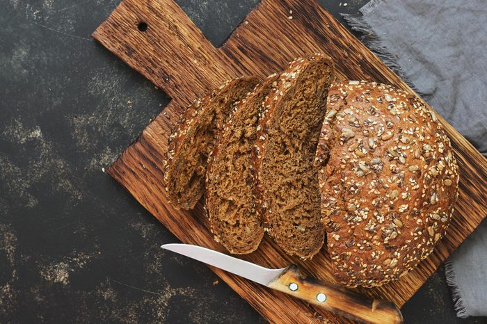 Fresh bread with sunflower seeds, sesame seeds and flax are cut into pieces on a cutting board. Top view, copy space