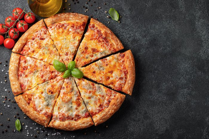 Delicious Italian pizza four cheeses with Basil, tomatoes and olive oil on a dark concrete table. Top view with copy space. Flat lay