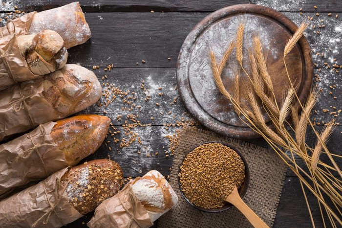 Bread background. Brown and white whole grain loaves wrapped in kraft paper composition on rustic dark wood with empty desk copy space. Baking and home bread making concept. Soft toning