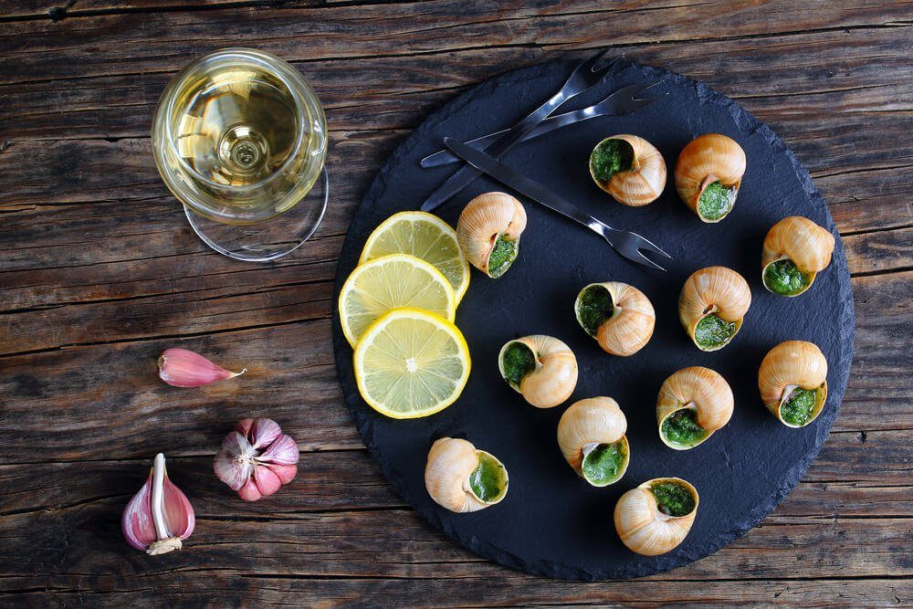 gourmet dish - Escargots de Bourgogne or Snails with herbs, butter, garlic on black slate plate with forks, ingredients and wine glass with dry white wine on wooden table, horizontal view from above