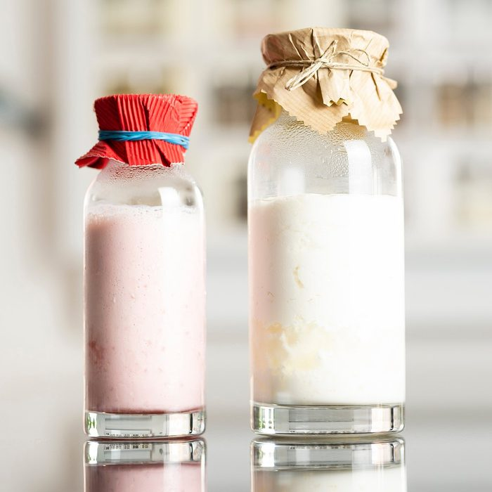 side view of glass bottles with a homemade raspberry smoothie with kefir yogurt and regular kefir yogurt with paper covers and kitchen shelf with spices in the background