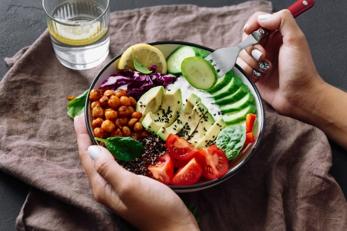 Woman is eating healthy lunch on dark background. Buddha bowl. Clean and balanced healthy food concept