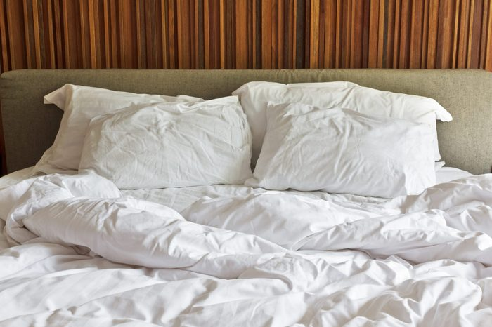 Messy white bed and two pillow, in the morning.