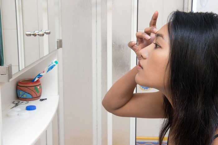 Woman looking at her reflection in the mirror. Side view portrait of a woman from the bathroom. Woman looks in the mirror in the bathroom. Concentrated beautiful Asian woman looks in the mirror.