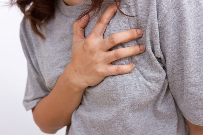 Severe heartache, woman suffering from chest pain, having heart attack or painful cramps, pressing on chest with painful expression.