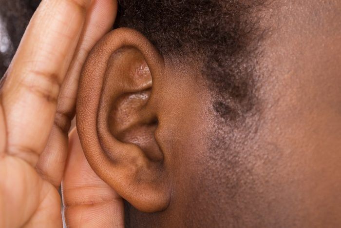 Close-up Of An African Woman Trying To Hear With Hand Over Ear