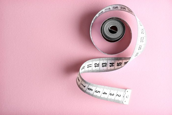 Measuring tape on pink background