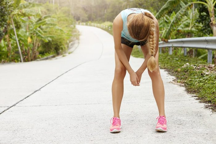 Tired woman runner having rest after running hard on road in forest, bending forward, resting elbows on her knees. Exhausted blonde sporty girl catching her breath after active fitness training