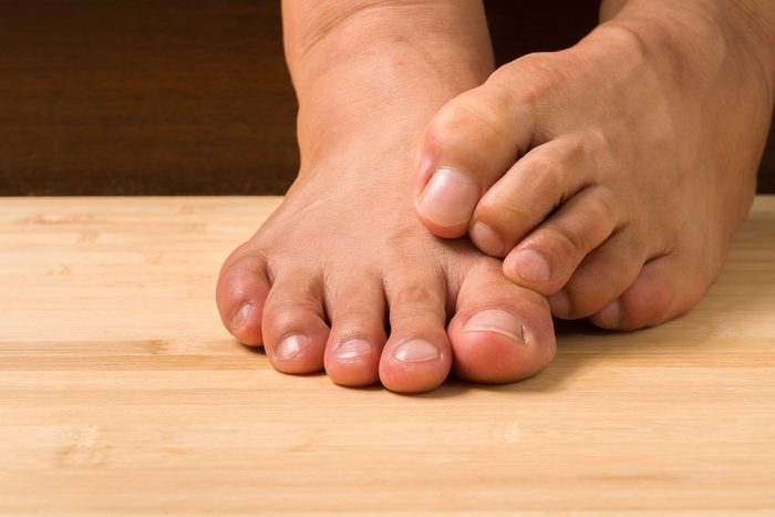 Closeup a man with itchy feet uses his big toe to scratch his other foot on wooden floor.