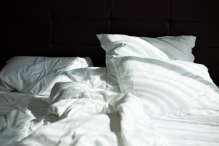 Messy bedding sheets and pillows, sunshine through window in the morning