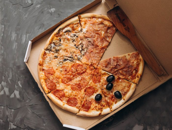 Close-up of a pizza in a carton box. Traditional italian pizza on a gray background. Nutritious foods. Pizza delivery.