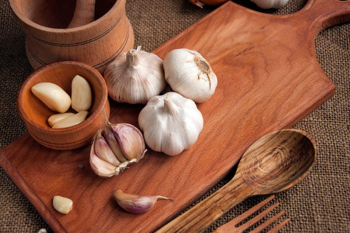 Heads of garlic, sliced garlic, and garlic cloves on a wooden cutting board, surrounded by wooden utensils like spoons and forks.