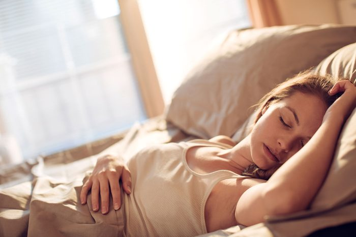 woman sleeping on her back in bed