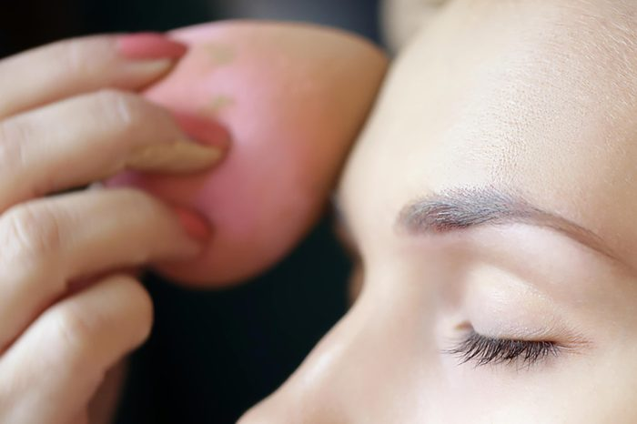 A woman applying foundation to her forehead with a pink beauty blender. | These skin care ingredients can cause breakouts.