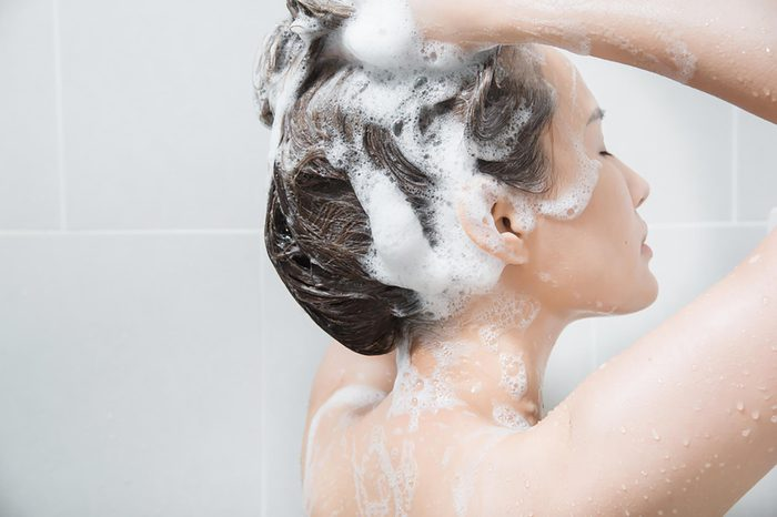 A woman shampooing her hair in the shower. | These skin care ingredients can cause breakouts.