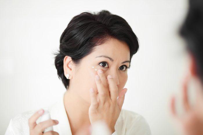Beautiful female applying facial treatment or cream around her eyes.