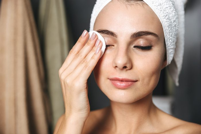 Beautiful young woman wrapped in bath towel standing at the bathroom, removing makeup with a cotton pad