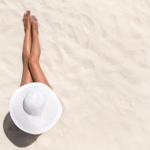 Summer holiday fashion concept - tanning woman wearing sun hat at the beach on a white sand shot from above
